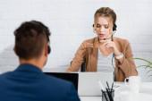 Žena operátorka ve sluchátkách mluvit, zatímco sedí na pracovišti s notebooky v kanceláři na rozmazané popředí