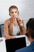 Positive Bedienerin im Headset blickt Kollegin an, während sie am Tisch sitzt, digitale Geräte im verschwommenen Vordergrund