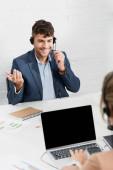 Usmívající se operátor ve sluchátkách gestikuluje, zatímco sedí na pracovišti s rozmazaným kolegou na popředí