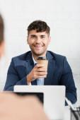 Usmívající se podnikatel s papírovým kelímkem při pohledu na kolegu, zatímco sedí na pracovišti na rozmazané popředí