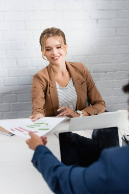 Smiling businesswoman giving paper sheet with charts to colleague, while sitting at workplace on blurred foreground stock vector