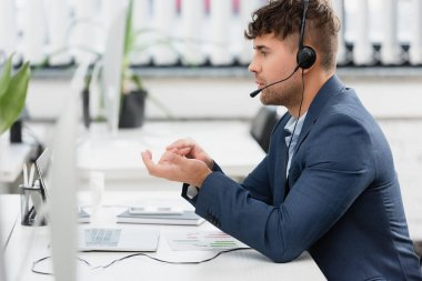 Side view of man in headset gesturing, while looking at laptop at workplace on blurred foreground stock vector