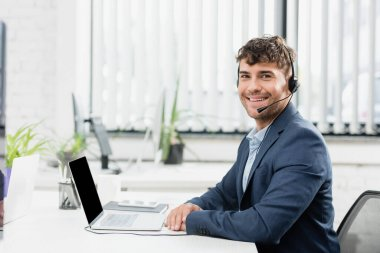 Cheerful consultant in headset looking at camera, while sitting at table with digital devices on blurred background