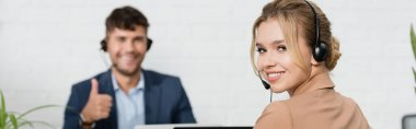 Smiling female operator in headset looking at camera with blurred colleague on background, banner stock vector