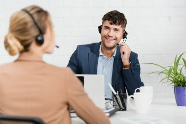 Smiling operator in headset looking at camera, while sitting at workplace with blurred colleague on foreground stock vector