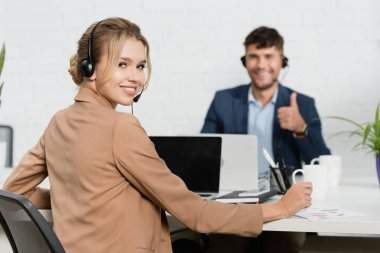 Smiling woman in headset looking at camera, while sitting at workplace with blurred colleague on background stock vector