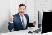 Excited businessman with yes gesture looking at camera, while sitting at workplace