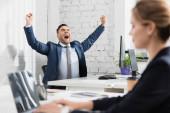 Nadšený manažer s gestem ano sedí na pracovišti s rozmazaným kolegou v popředí