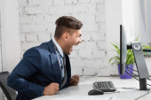 Šokovaný obchodník s otevřenými ústy při pohledu na monitor počítače, zatímco sedí na pracovišti
