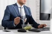 Oříznutý pohled na podnikatele jíst jídlo z plastové misky, zatímco psaní na klávesnici počítače na pracovišti