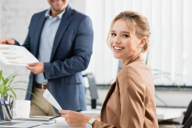 Happy businesswoman with document looking at camera, while sitting at workplace with blurred colleague on background stock vector