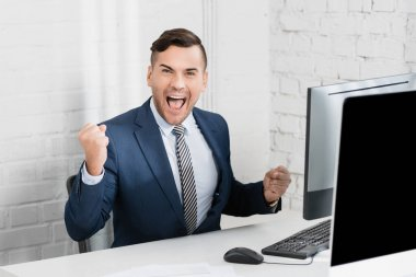 Excited businessman with yes gesture looking at camera, while sitting at workplace stock vector