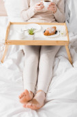 cropped view of woman with vitiligo holding cup near breakfast on tray