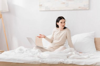 displeased woman with vitiligo pointing with hand at laptop on bed
