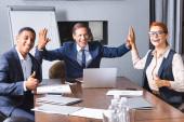 Happy businessman giving high five to multikulturní kolegové s palcem nahoru na pracovišti v zasedací místnosti