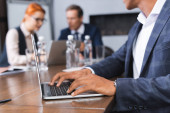 African american businessman typing on laptop at workplace with blurred colleagues on background