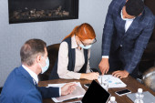 Redhead executive writing on document near multicultural businesspeople in boardroom