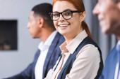 Lächelnde rothaarige Geschäftsfrau mit Brille blickt in die Kamera, mit verschwommenem afrikanisch-amerikanischem Kollegen im Hintergrund
