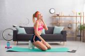 Glückliche junge Sportlerin mit händchennaher Wange, die zu Hause auf der Fitnessmatte in die Kamera schaut