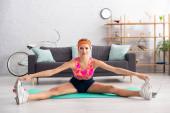 Mladé blondýny sportovkyně při pohledu na kameru, zatímco dělá split na fitness podložku doma