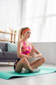 Plná délka mladé sportovkyně sedí v lotosu pózovat na fitness podložku doma na rozmazaném pozadí