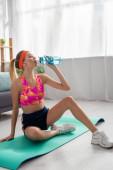 Plná délka mladé blondýny sportovkyně pitné vody ze sportovní láhve, zatímco sedí na fitness podložka na rozmazaném pozadí