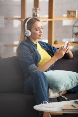 Young blonde woman in headphones texting on smartphone while sitting on couch on blurred background stock vector