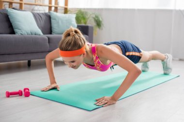 Full length of positive sportswoman doing press ups on fitness mat on blurred background stock vector