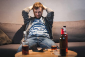 drunk man sitting near table with alcohol drinks and empty wallet on blurred foreground