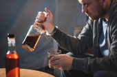 závislý muž, připoutaný k láhvi whisky, rozmazané popředí