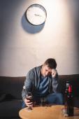 depresivní muž drží láhev whisky, zatímco sedí doma sám
