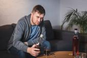 opilý muž dívá na kameru, zatímco drží láhev whisky doma