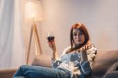 opilá, skeptická žena hledící na kameru, zatímco sedí se sklenicí červeného vína