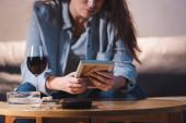 kivágott kilátás depressziós nő gazdaság képkeret üveg közelében vörösbor, homályos háttér