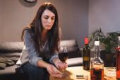 frustrovaná žena držící snubní prsten a sklenici červeného vína v blízkosti lahví na rozmazaném popředí