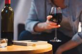Flasche Alkohol, Fotorahmen und Ehering in der Nähe einer Frau mit einem Glas Rotwein auf verschwommenem Hintergrund