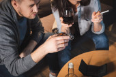 alkoholem závislý manžel a manželka pití v blízkosti prázdné peněženky na stole