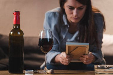 Depressed woman looking at photo frame while sitting near bottle and glass of red wine, blurred background stock vector