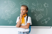 Photo Schoolgirl with backpack looking away near green chalkboard with school icons illustration