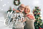 šťastný starší pár objímání při pohledu na kameru v blízkosti veselých vánoc každý nápis a dekorace na rozmazaném pozadí