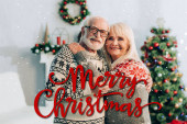 happy senior couple embracing while looking at camera near merry christmas lettering and decorations on blurred background
