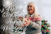 vidám idős nő bemutató ajándék a férj közelében boldog karácsonyt és boldog új évet betű