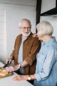 mosolygó idősebb férfi nézi a nőt, miközben vágás sajt vágódeszka a konyhában
