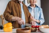 levágott kilátás idős feleség közelében férj vágás cseresznye paradicsom a konyhában elmosódott előtérben