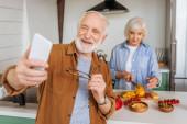 boldog idős férj okostelefonnal selfie feleséggel főzés vacsora a konyhában elmosódott előtérben