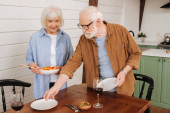 smiling senior couple serving table with plates and salad in kitchen on blurred background