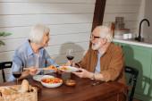 šťastný senior manželka s špachtle smích při podávání salát pro manžela u stolu s večeří na rozmazaném pozadí