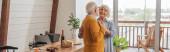 usmívající se starší pár tančící u stolu s vegetariánskou večeří v kuchyni, banner