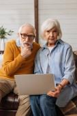 figyelmes idős pár laptop nézi a kamerát, miközben ül a kanapén homályos háttér otthon