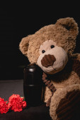 Photo carnation, teddy bear and urn with ashes on black background, funeral concept